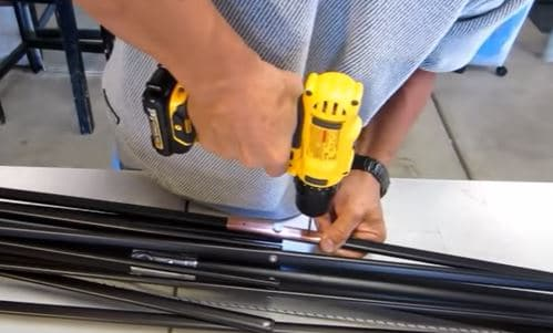 repair a patio umbrella - drill two holes with drill